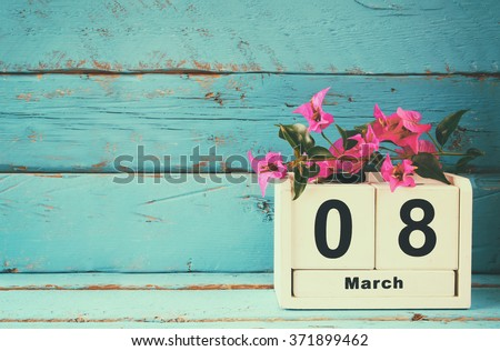 wooden March 8 calendar, next to purple flowers on old blue rustic table. selective focus. vintage filtered - stock photo