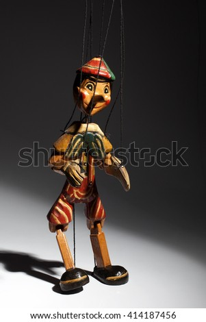 Wooden marionette of Pinocchio liar with big nose. Dramatic light. - stock photo