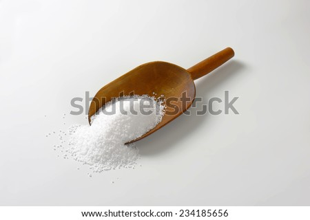 wooden measuring spoon with portion of salt - stock photo