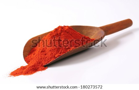 wooden measuring spoon with scattered red pepper - stock photo