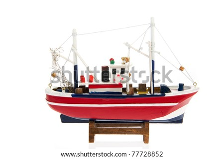 Wooden miniature fishing trawler boat isolated over white background - stock photo