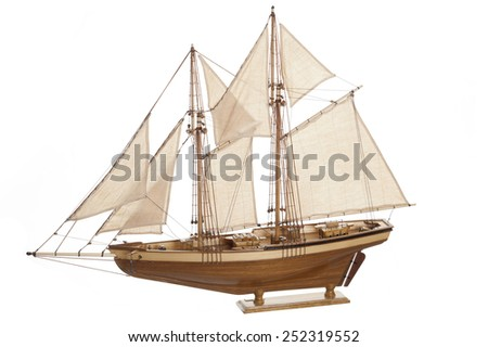 Wooden model ship with sails on a white background.
