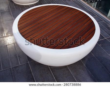 Wooden modern trendy design round circular street bench - stock photo