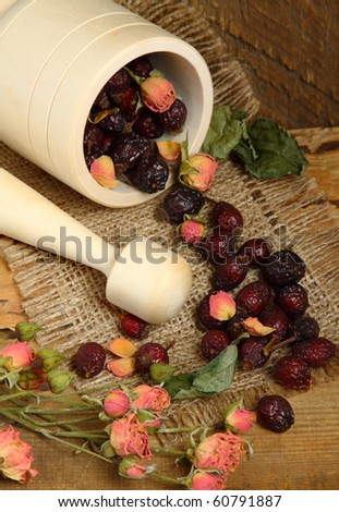 Wooden mortar and scattered rose hips on the sacking - stock photo