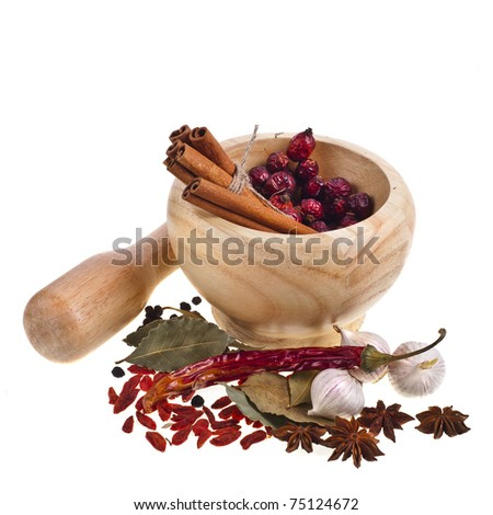 Wooden mortar, dogrose berries and spices isolated on white background - stock photo