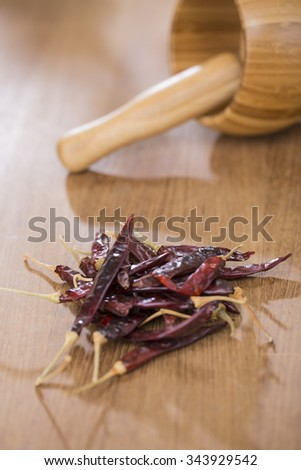 Wooden Mortar with pestle with red chilies on wooden table.  - stock photo