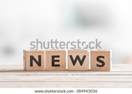 Wooden news sign on a table in an office - stock photo