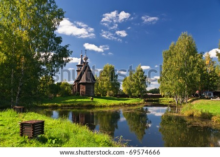 Wooden old church in park. Autumnal landscape - stock photo