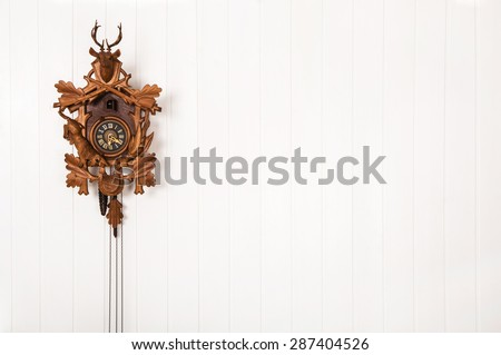 Wooden old cuckoo clock hanging on a white wall. - stock photo