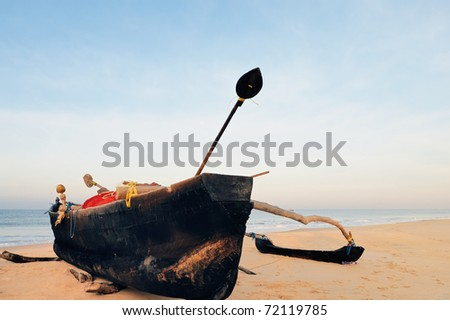 Wooden old fishing boat on the sandy shore - stock photo