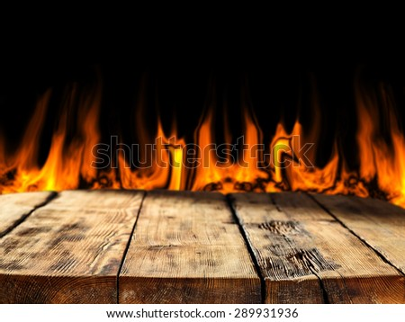wooden old table shadows and fire place  - stock photo