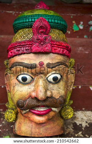Wooden old vintage head of statue from Rajasthan in flee market. - stock photo