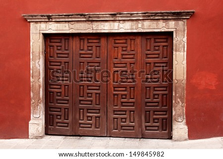 wooden ornament gate in red wall. mexican architecture - stock photo