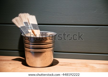 Wooden Paint Brush in the Silver Cup on the Wood Shelf and Green Background