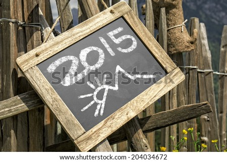 Wooden palisade with chalkboard hint panel. Chalkboard with 2015 date - stock photo