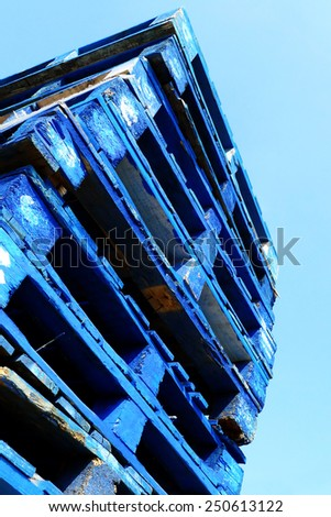Wooden pallets; pile of wooden industrial pallets isolated against blue sky  - stock photo