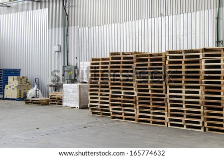 Wooden pallets stacked inside a warehouse  - stock photo