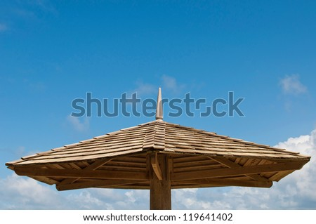 wooden parasol against a blue sky background (copy-space available) - stock photo