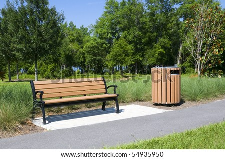 Wooden park bench and trash container in a natural setting - stock photo