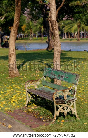 Wooden park bench under tree and near a lake. - stock photo