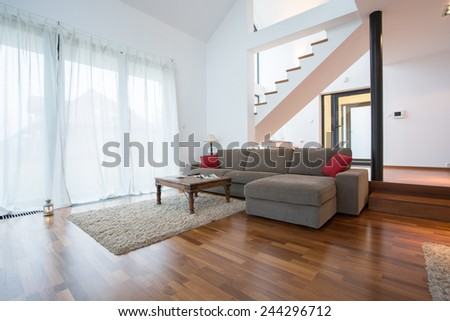 Wooden parquet and small carpet in living room - stock photo