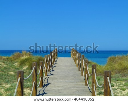 wooden path leading through the dunes to the sea - stock photo