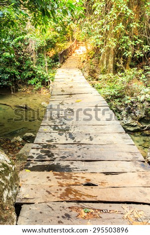 Wooden pathway over waterfall in forest.