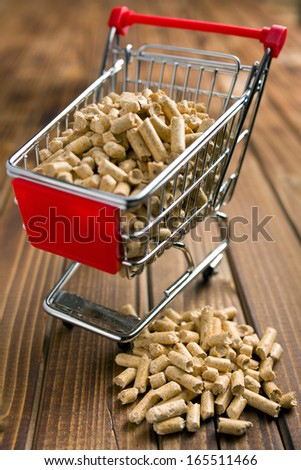 wooden pellets in shopping cart on wooden background - stock photo