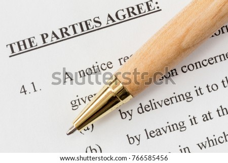 Wooden pen over a printed agreement
