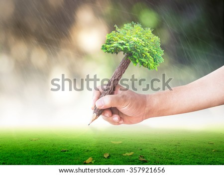 Wooden pencil in hand on blurred bokeh beautiful house on heavy rain with sunset background. Ecology Biological World Environment Day Services Insurance Finance CSR Education Business Trust concept - stock photo