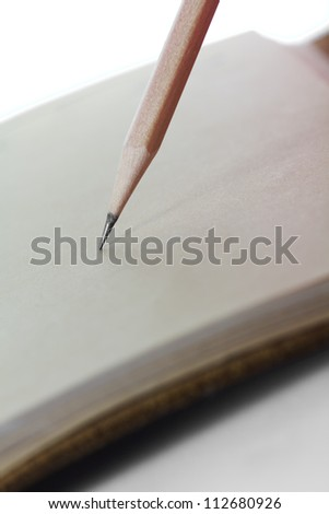 wooden pencil writing on brown paper book - stock photo