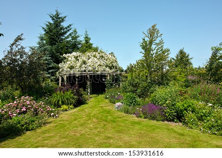 Wooden pergola gazebo in a beautiful blooming garden full of flowers and green plants