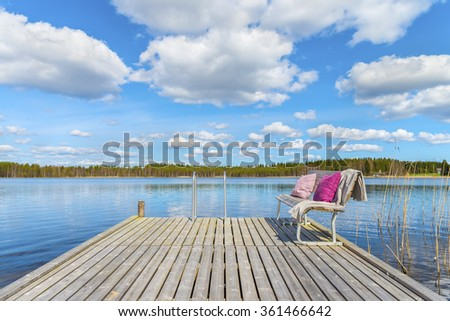 Wooden pier and cozy bench with soft blanket and pillows on a background of the  beautiful lake and forest at sunny day.Scenic natural landscape.Panoramic view.The land of lakes.Finland.Europe. - stock photo