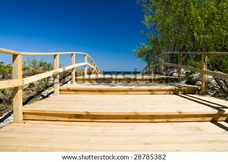 Wooden pier close to sunny beach and blue sky - stock photo