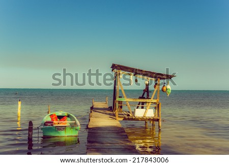wooden pier dock jetty shelter and boat in caye caulker belize caribbean - stock photo