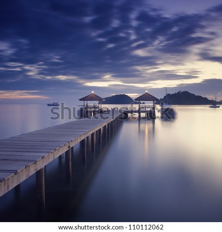 Wooden pier in a twilight atmosphere Long exposure photography in Koh-Mak island, Thailand