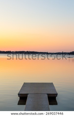 Wooden pier in the calm evening lake reflecting sunset colors - stock photo