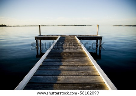 Wooden pier / jetty stretches out into an idyllic ocean - stock photo