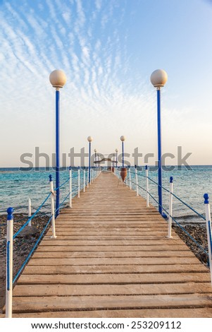 wooden pier leading to open blue sea - stock photo