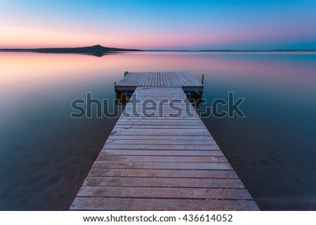 Wooden pier on a blue lake sunset and smooth reflection on water. Long exposure; Zerendi Lake; Kazakhstan.