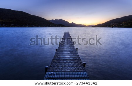wooden pier on big lake in Queenstown, New Zealand - stock photo