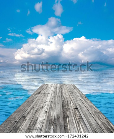 wooden pier on sunny day with white clouds and sun