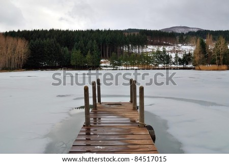 wooden pier over the frozen lake in the forest - stock photo