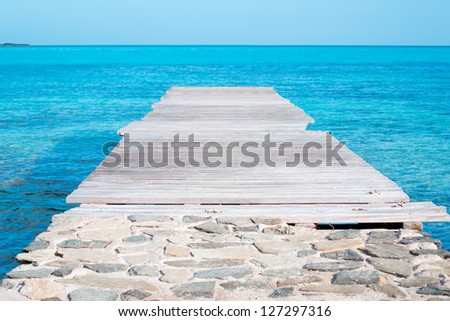 wooden pier over turquoise water in Sardinia - stock photo