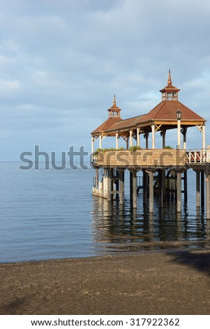 Wooden pier stretching out over the calm waters of Lake Llanquihue in the small town of Frutillar in southern Chile.