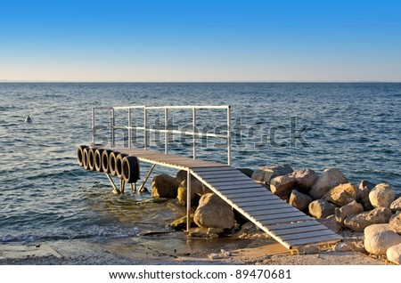 Wooden pier with tires on its side - stock photo