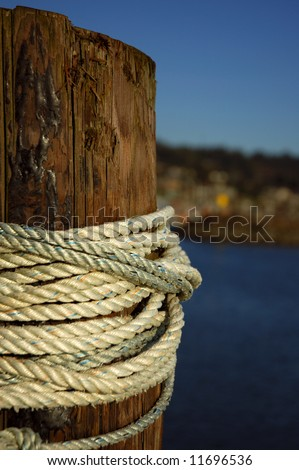 Wooden piling at dock wrapped with rope with marina in background - stock photo