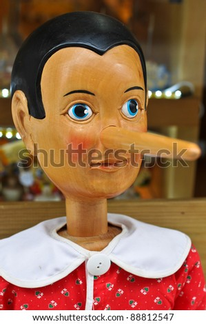 Wooden pinocchio doll with his long nose - stock photo