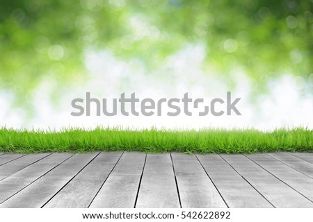 Wooden plank and bright spring green leave bokeh background