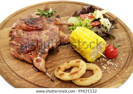 wooden plate with roasted quail and salad - stock photo